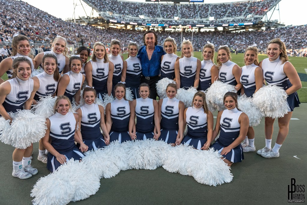 Neil Diamond impersonator Tom Sadge chosen by Penn State to perform. Shown with Penn State cheerleaders.
